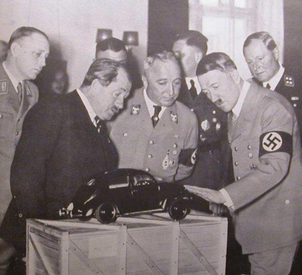 სურათზე: ჰიტლერი ეხება მისი დაბადების დღის საჩუქარს: ფოლკსვაგენის მოდელს. მის გვერდით: რობერტ ლეი და ფერდინანდ პორშე.